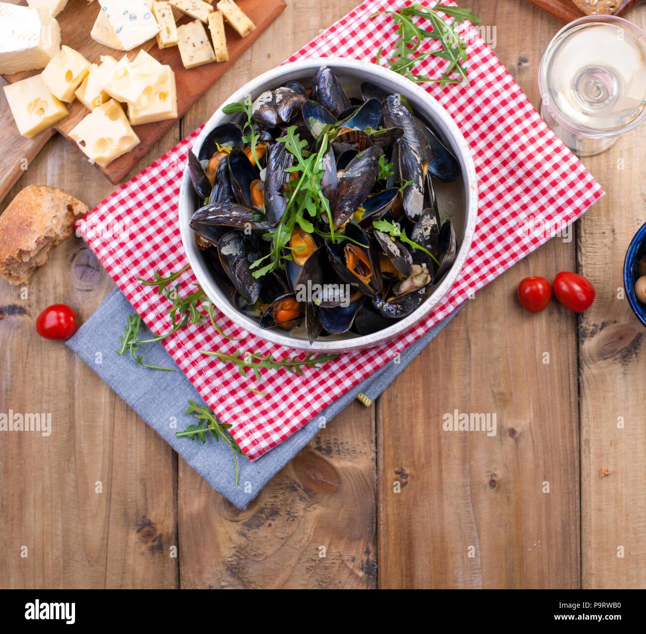 Müsli in einem weißen Keramik Schüssel, auf einem roten Serviette. Käse auf einem Holzbrett und Oliven, Brot. Auf einer hölzernen Hintergrund. Freier Platz für Text oder Werbung. Stockbild