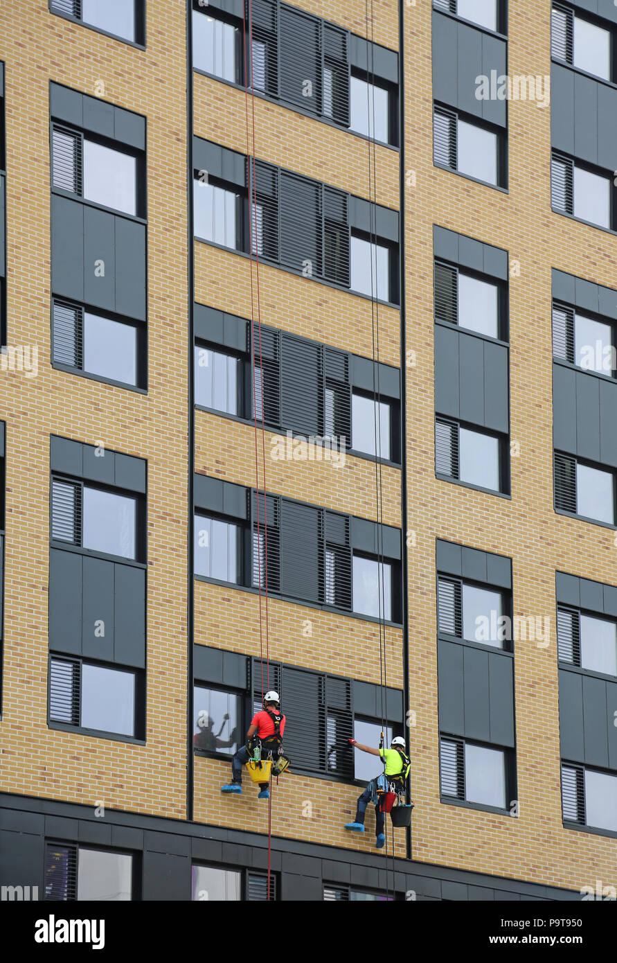 Zwei Fenster Reinigungsmittel verwenden abseilen Seile Windows auf ein neues Bürogebäude im Zentrum von Portsmouth, Hampshire, UK zugreifen Stockbild