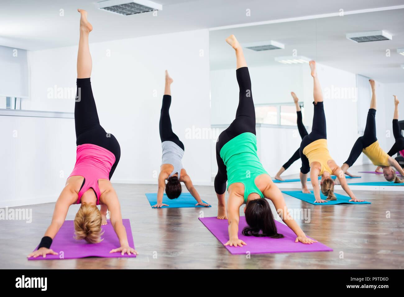 Vier Mädchen üben Yoga, Eka Pada Adho Mukha Svanasana/1-beinig Nach unten zeigender Hund darstellen Stockbild