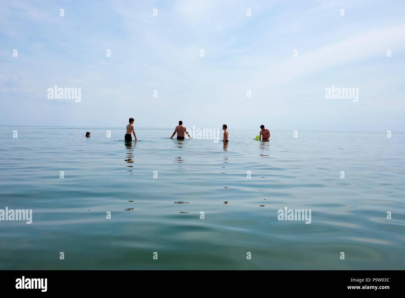 Querformat von vier Jungen und eines männlichen das Stehen bis zu ihren Hüften in einer ruhigen Mittelmeer, während ein Spiel das Spiel mit dem gelben Ball lachen Stockbild