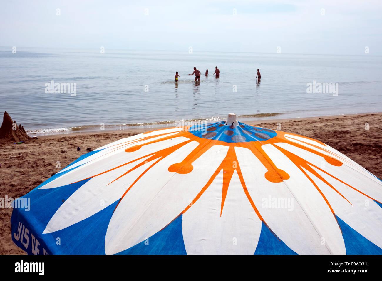 Querformat von Vater Ball spielen mit vier Jungen in einer ruhigen Mittelmeer stehend, mit 7/8-vintage Baumwolle Sonnenschirm am Strand im Vordergrund Stockbild