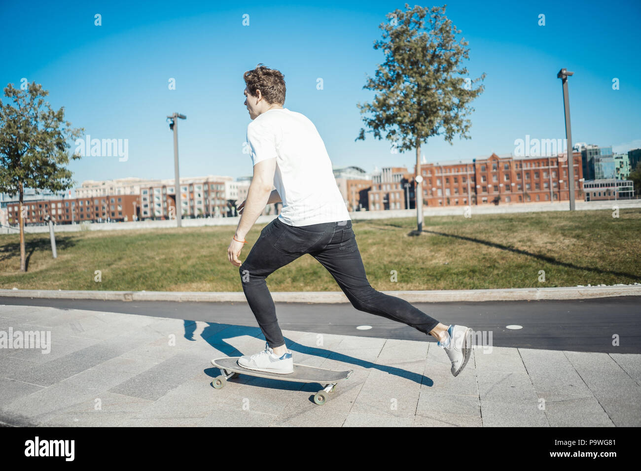 Jungen attraktiven Mann reiten Longboard im Park. Stockbild