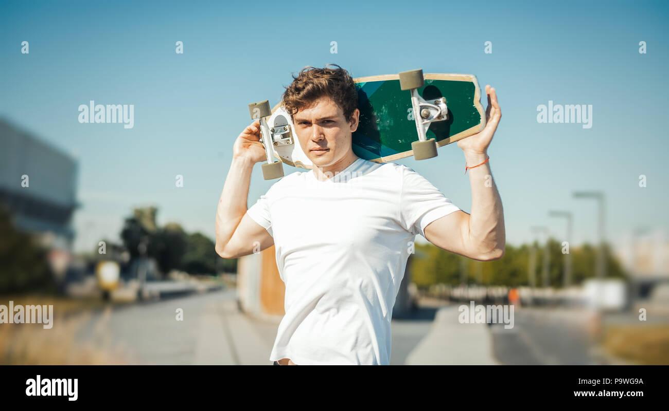 Jungen attraktiven Mann holding Longboard. Stockbild