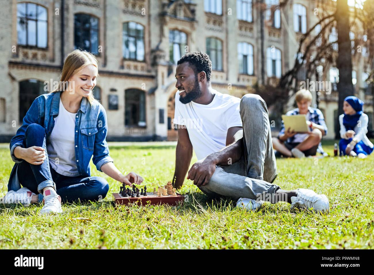 Fröhliche junge Menschen Schach spielen im Freien Stockbild