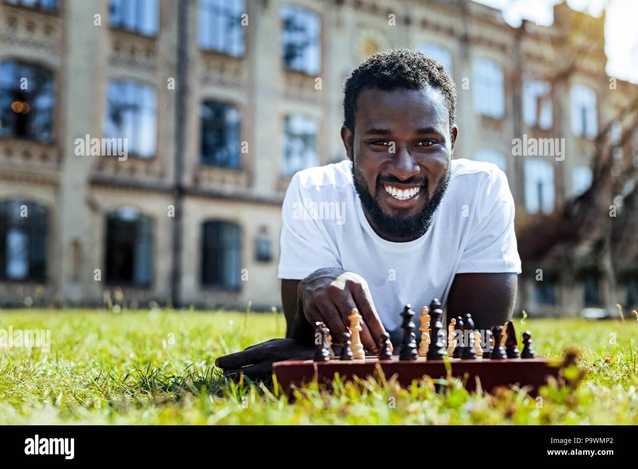 Strahlende junge Herr Schach spielen im Freien Stockbild