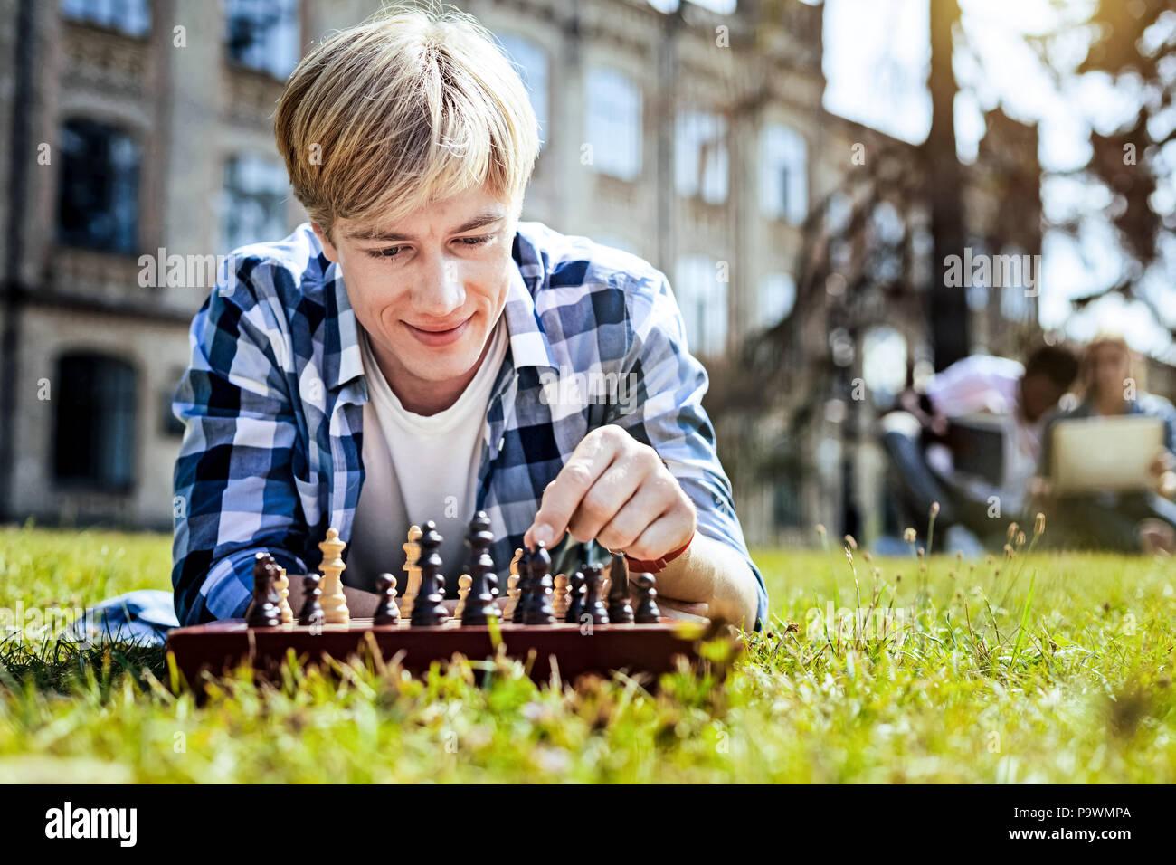 Hübscher junger Mann spielt Schach im Freien Stockbild