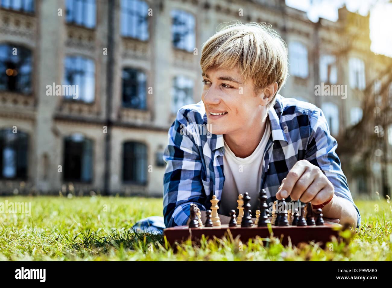 Nachdenklicher Kerl lächelnd während Schach spielen Stockbild