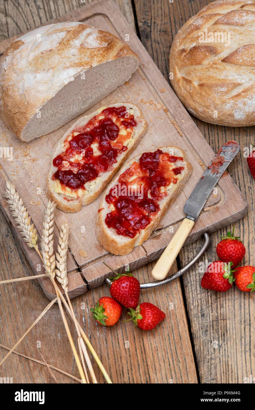 Erdbeermarmelade auf Brot mit Weizen und Erdbeeren auf einem Holz Hintergrund Stockbild