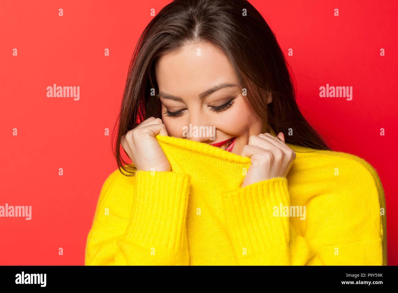 Schön schämen Frau in einem gelben Pullover auf rotem Hintergrund Stockbild