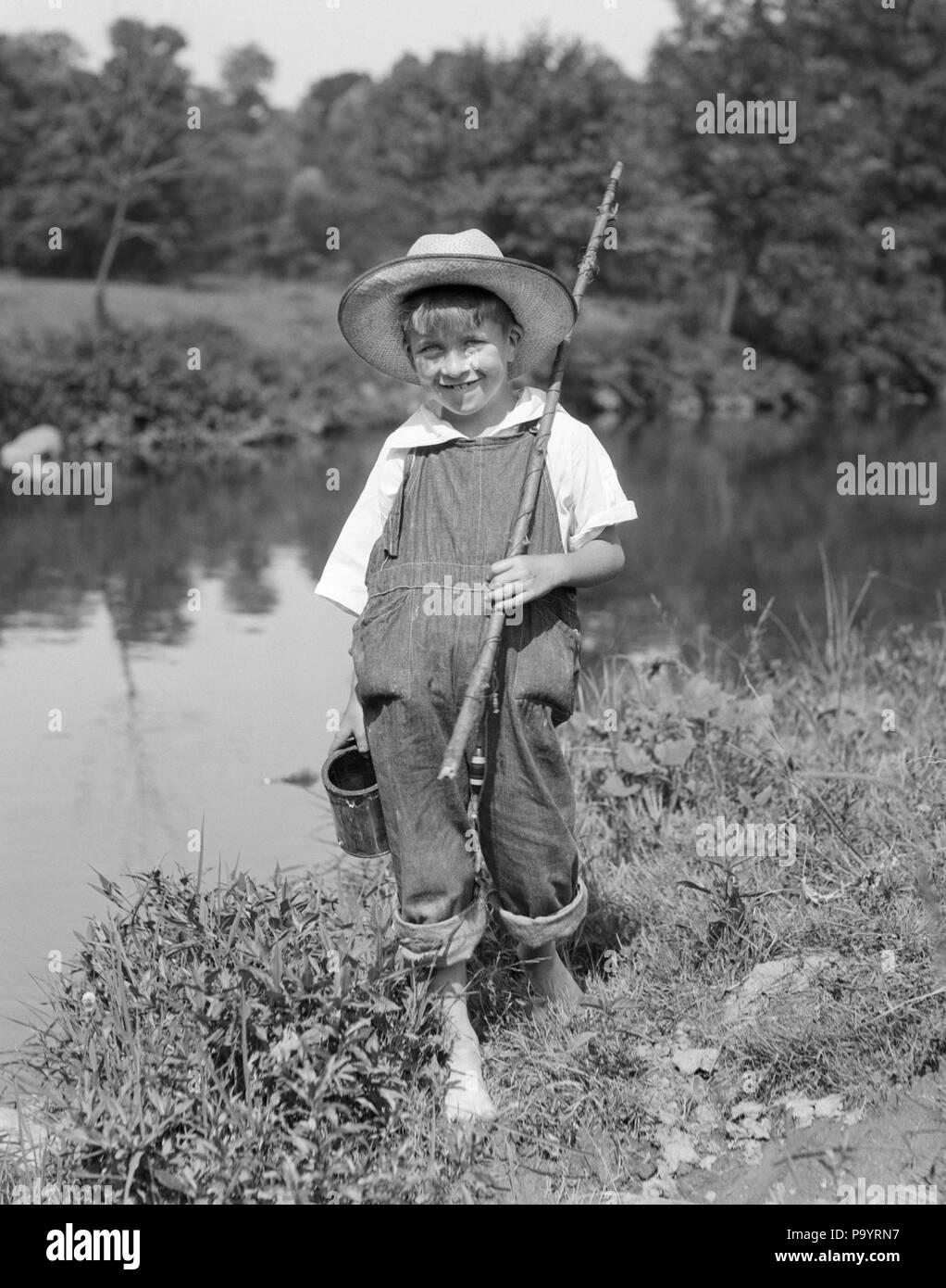 1920er Jahre 1930er Jahre barfüßigen Jungen mit STICK ANGELRUTE KANN DER KÖDER WÜRMER TRAGEN STROHHUT BIB OVERALLS in die Kamera lächeln - Eine 4795 HAR 001 HARS KOPIE RAUM VOLLER LÄNGE OVERALLS STREAM MÄNNER STANGE DENIM B&W SOMMER AUGENKONTAKT FREIHEIT GLÜCK FRÖHLICHEN ABENTEUER FREIZEIT BARFUSS LÄCHELT nackte Füße HUCK FINN FREUDIGE BIB OVERALLS TOM SAWYER Huckleberry Finn Jugendliche vor - jugendlich vor - jugendlich Junge WÜRMER KÖDER SCHWARZ UND WEISS KAUKASISCHEN ETHNIE HAR 001 ALTMODISCH Stockfoto