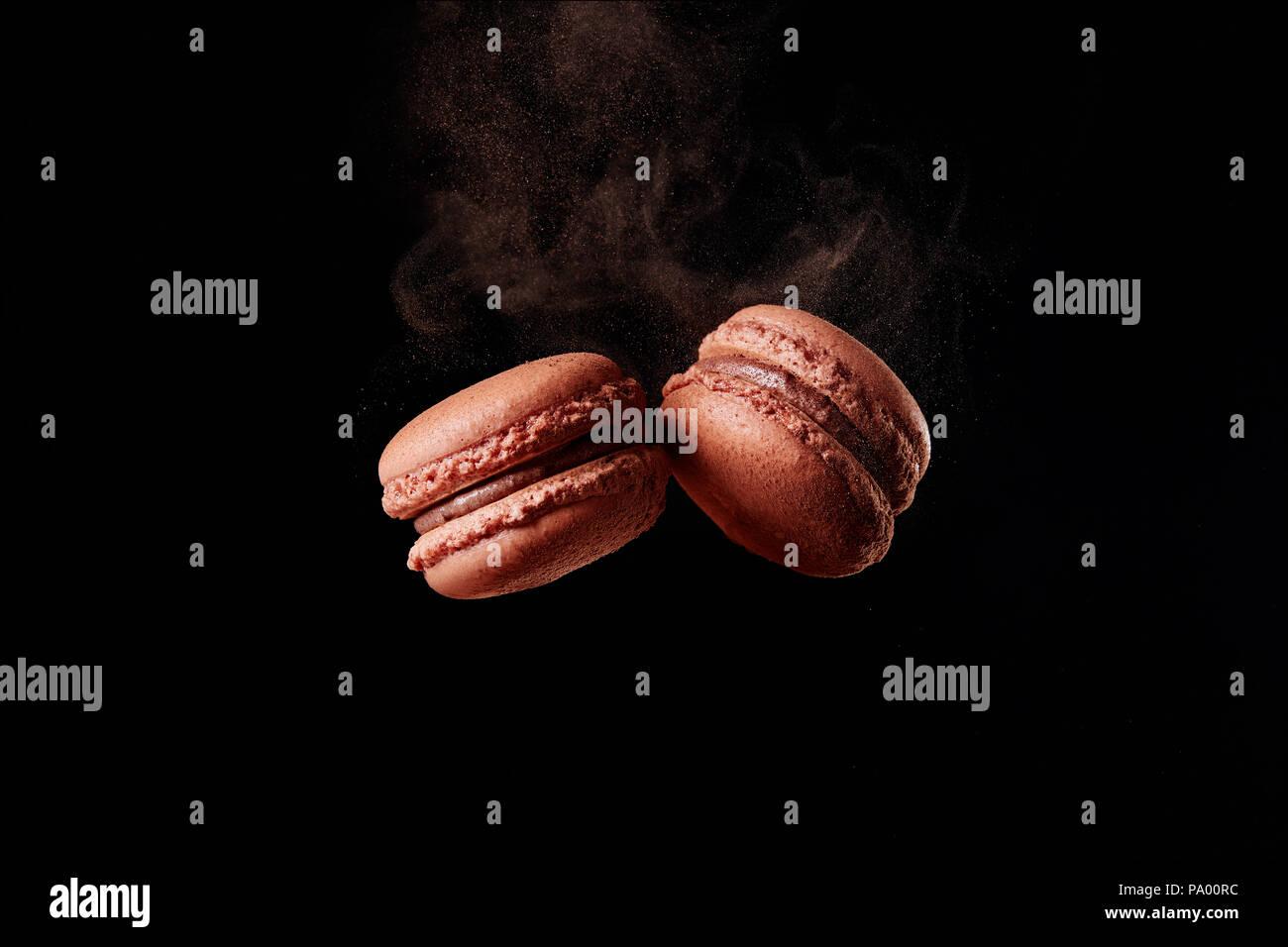 Französische Schokolade Macaron mit Kakaopulver auf schwarzem Hintergrund Stockbild