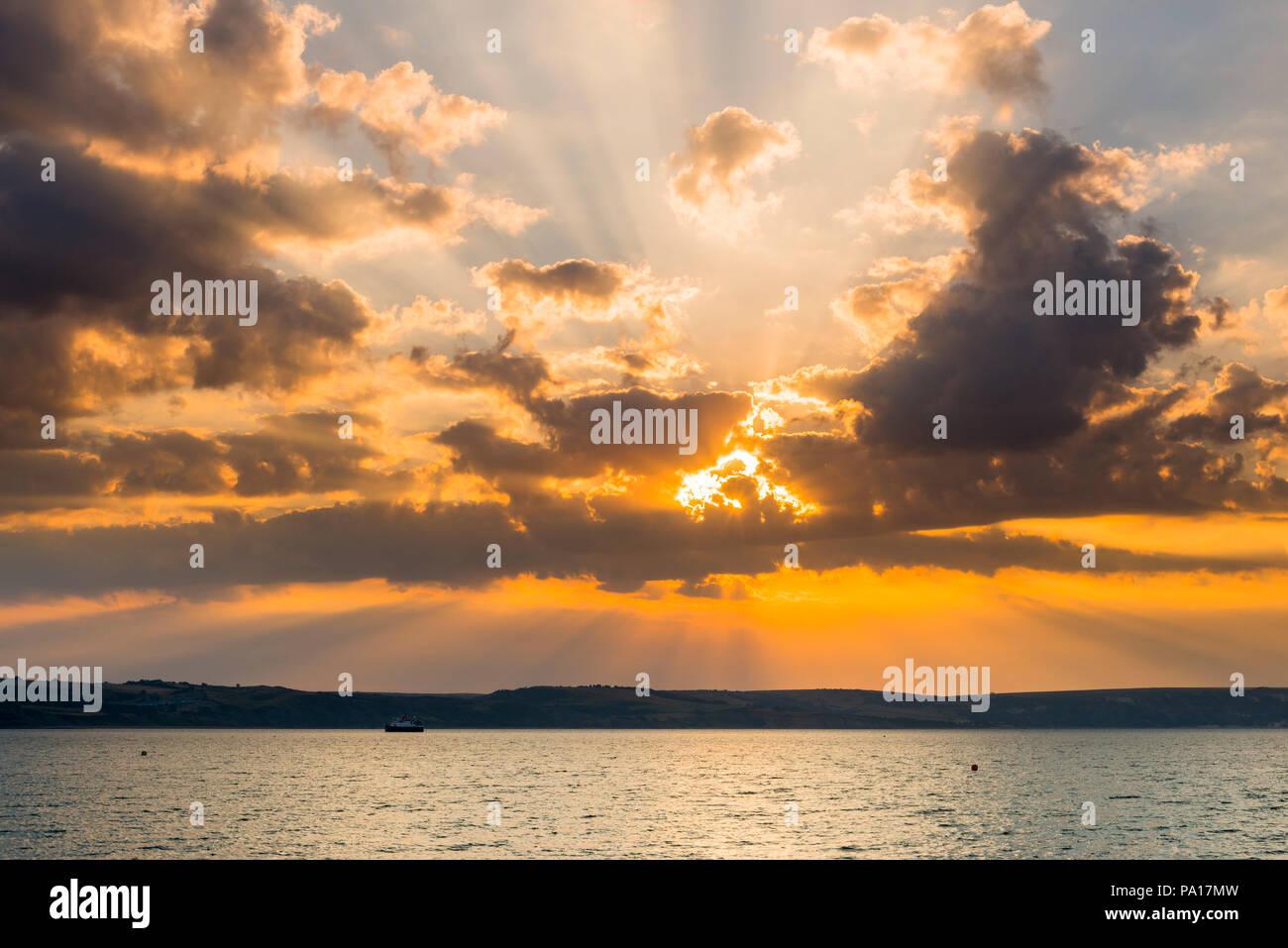 Dorchester, Dorset, Großbritannien. Juli 2018 20. UK Wetter. Sonnenstrahlen Strahlen hinter Wolken am frühen Morgen in den Badeort Weymouth in Dorset an einem warmen abgerechnet. Foto: Graham Jagd-/Alamy leben Nachrichten Stockbild