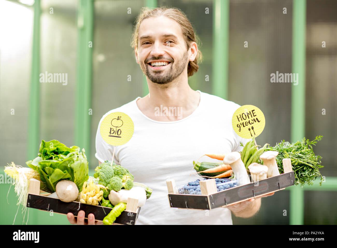 Portrait von ein stattlicher Mann mit Kisten voller Frische rohe Gemüse stehen draußen auf der grünen Wand Hintergrund Stockbild