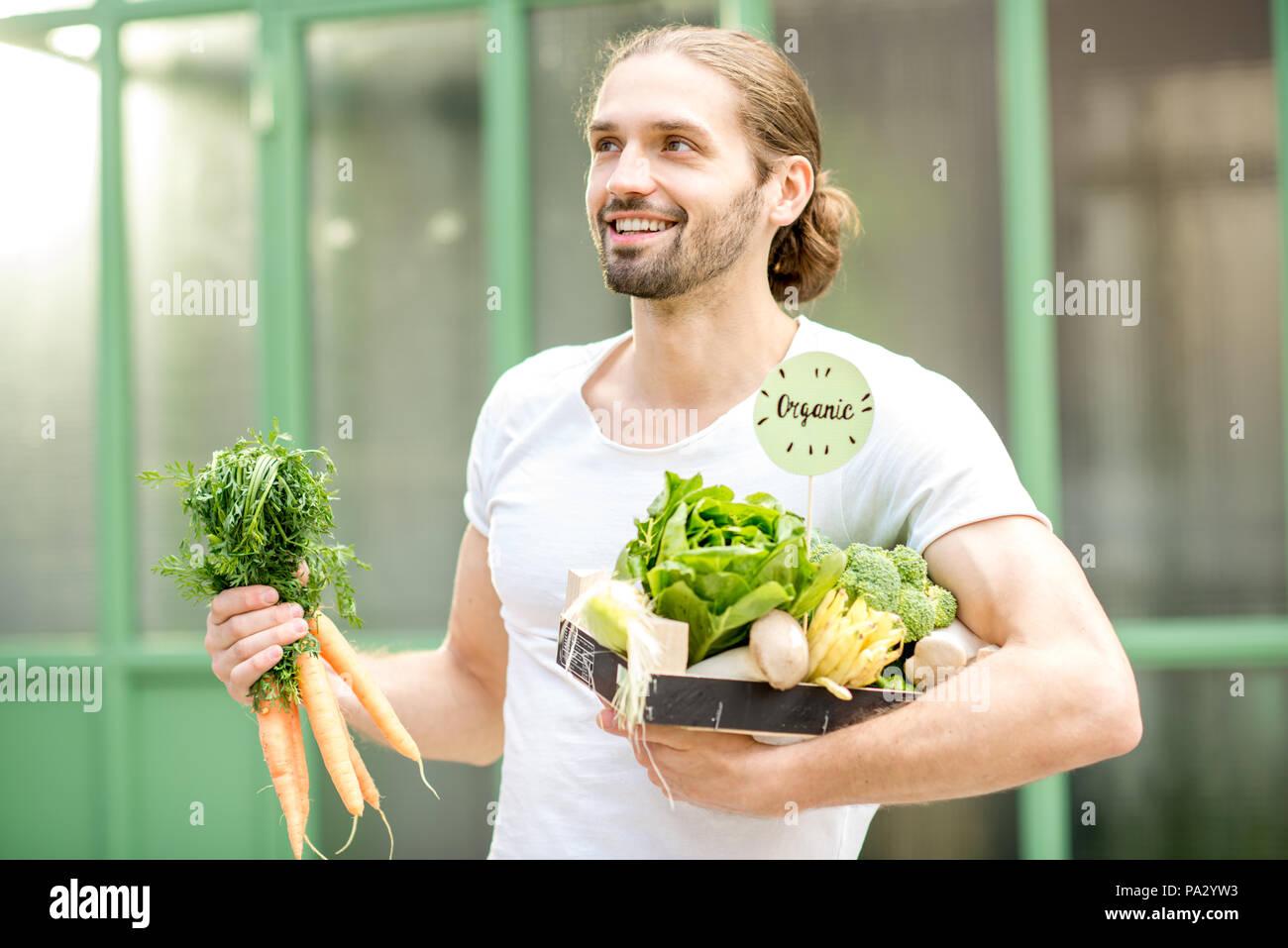 Portrait Of Happy vegetarisch Mann Holding Box voller Frische rohe Gemüse im Freien auf der grünen Hintergrund Stockfoto