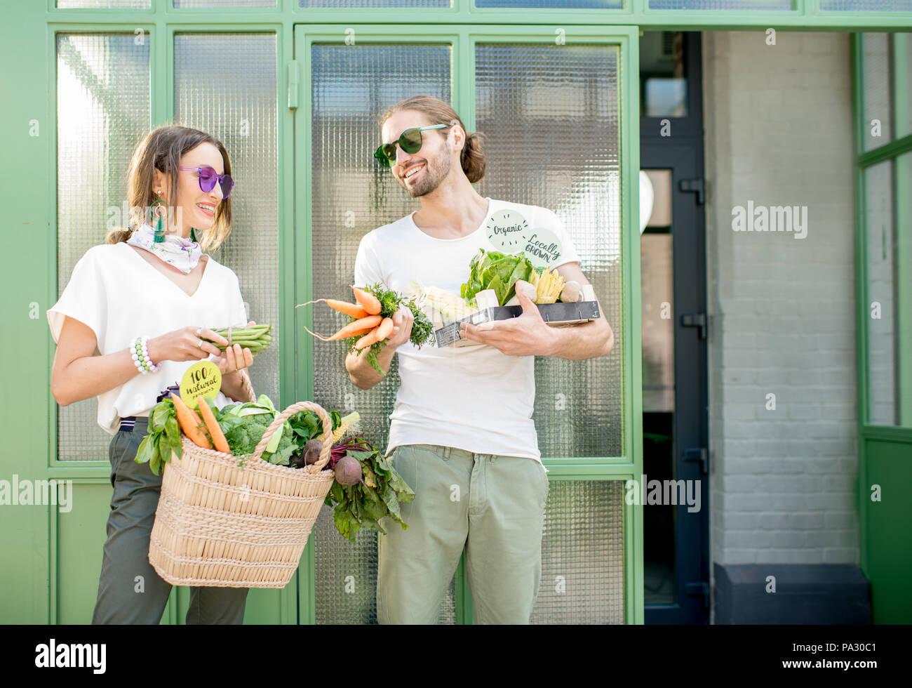 Junge vegetarische Paar stehen zusammen mit Beutel und Kasten voll Frische rohe Produkte vom lokalen Markt im Freien auf der grünen Hintergrund Stockbild