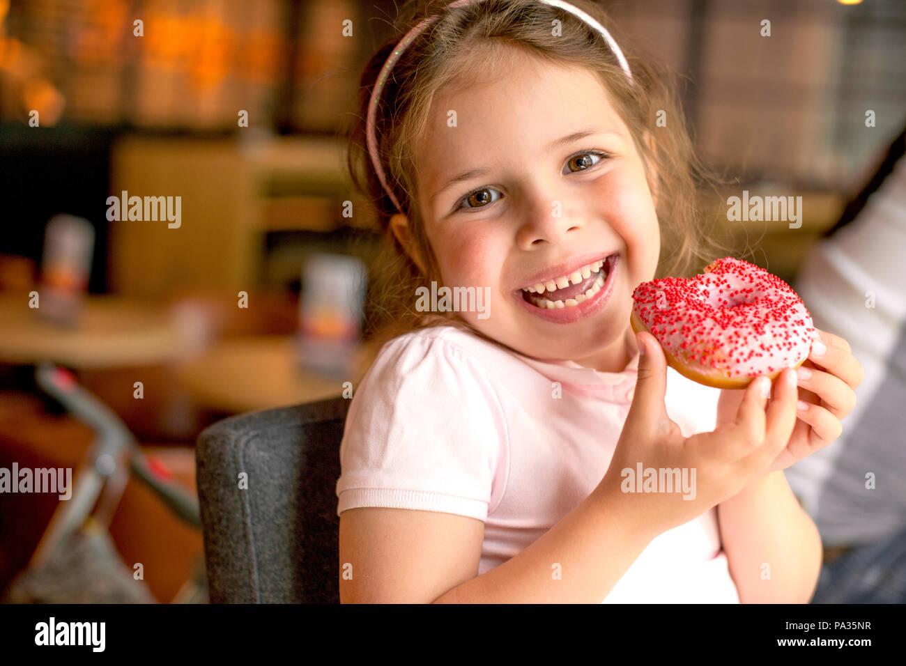 Happy girl essen Kuchen in einem Cafe. Schädliche süße Speisen. Trends in der Nahrung. Platz kopieren Stockbild
