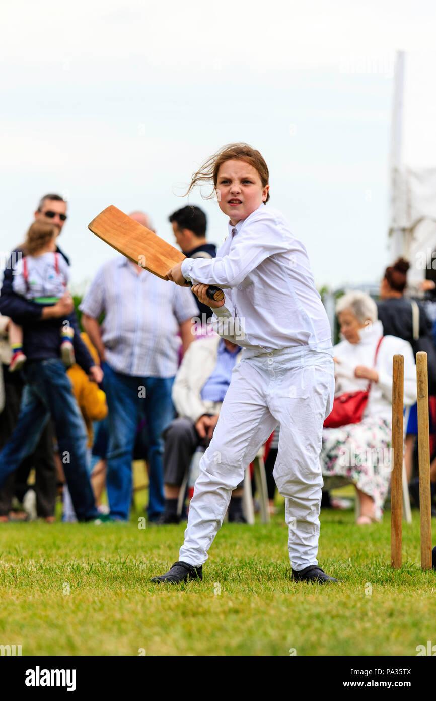 Junge Mädchen, Kind, 12-13 Jahre, Schlagen mit Cricket bat, während Sie im viktorianischen Kostüm während Cricket Match gekleidet. Broadstairs Dickens Woche Festival Stockbild