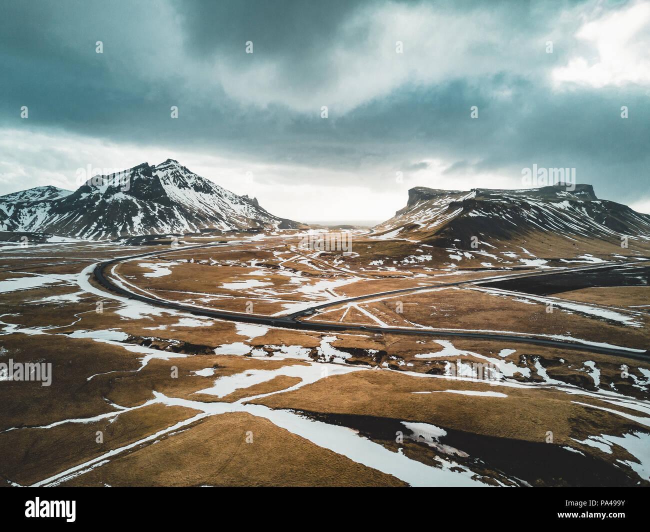 Island Luftaufnahme Landschaft mit Schnee und Wolken-, Street- und Gelbes und grünes Gras Stockbild