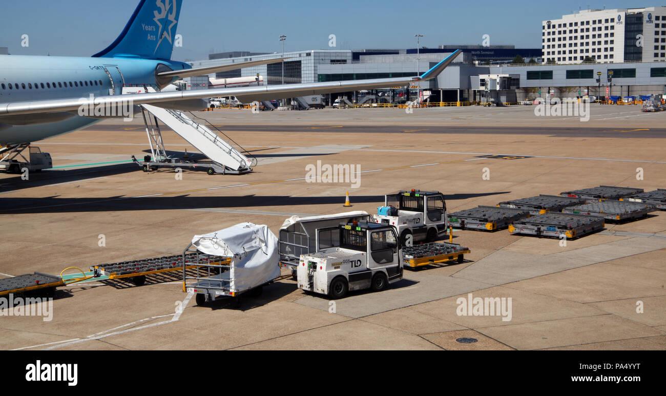 Ausrüstung Gepäck auf dem Vorfeld am Flughafen London Gatwick zu handhaben Stockbild