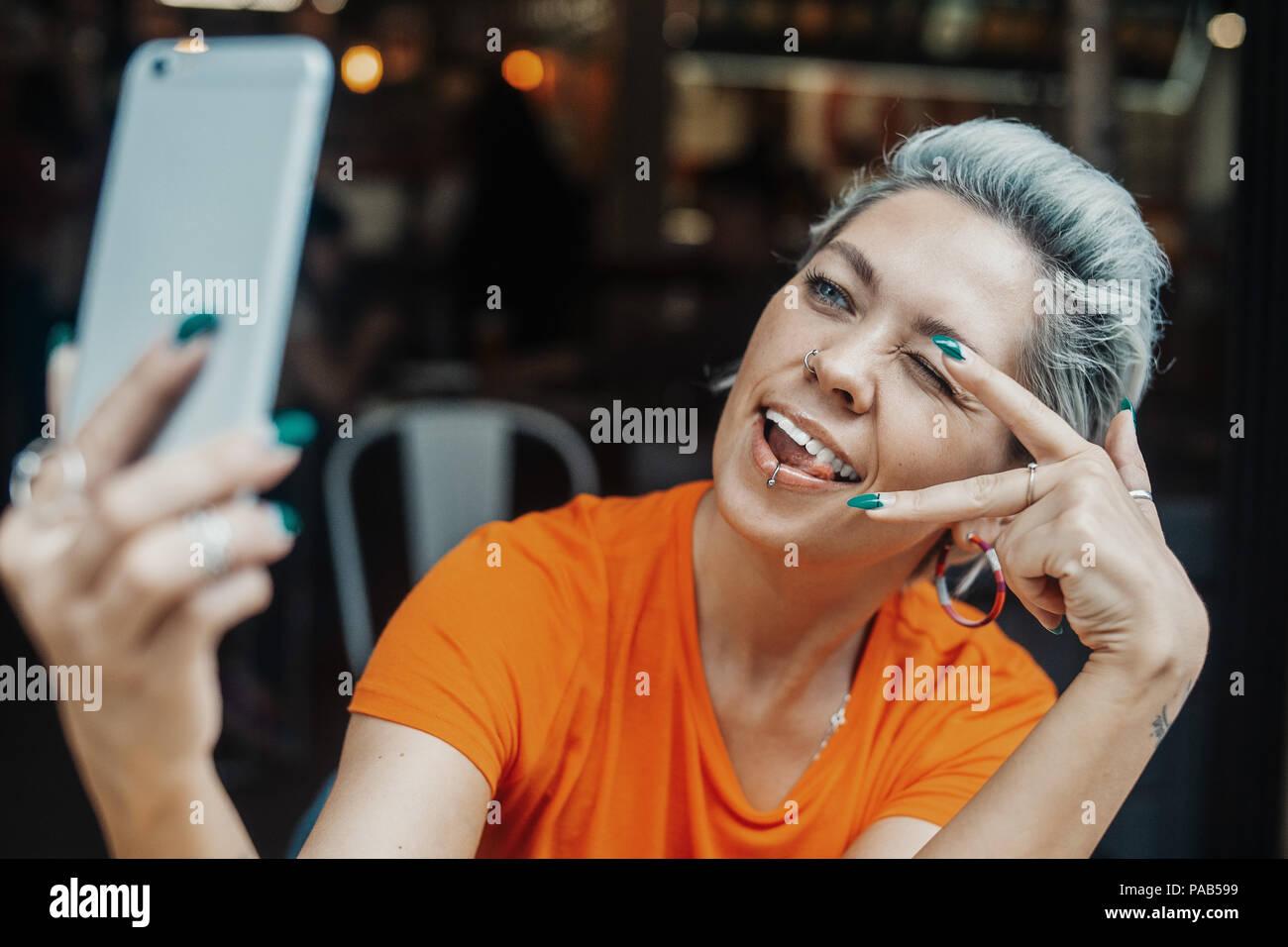 Attraktive blonde Frau, die selfie im Cafe und Zeichen des Sieges Stockbild