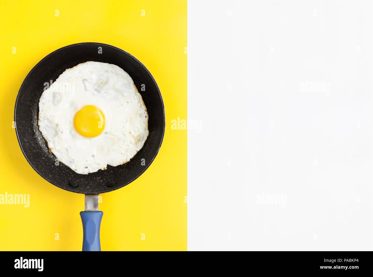 Frisch gekochtes Ei in einer Pfanne auf Split Farbe gelb und weißem Hintergrund, flach Bild. Stockbild