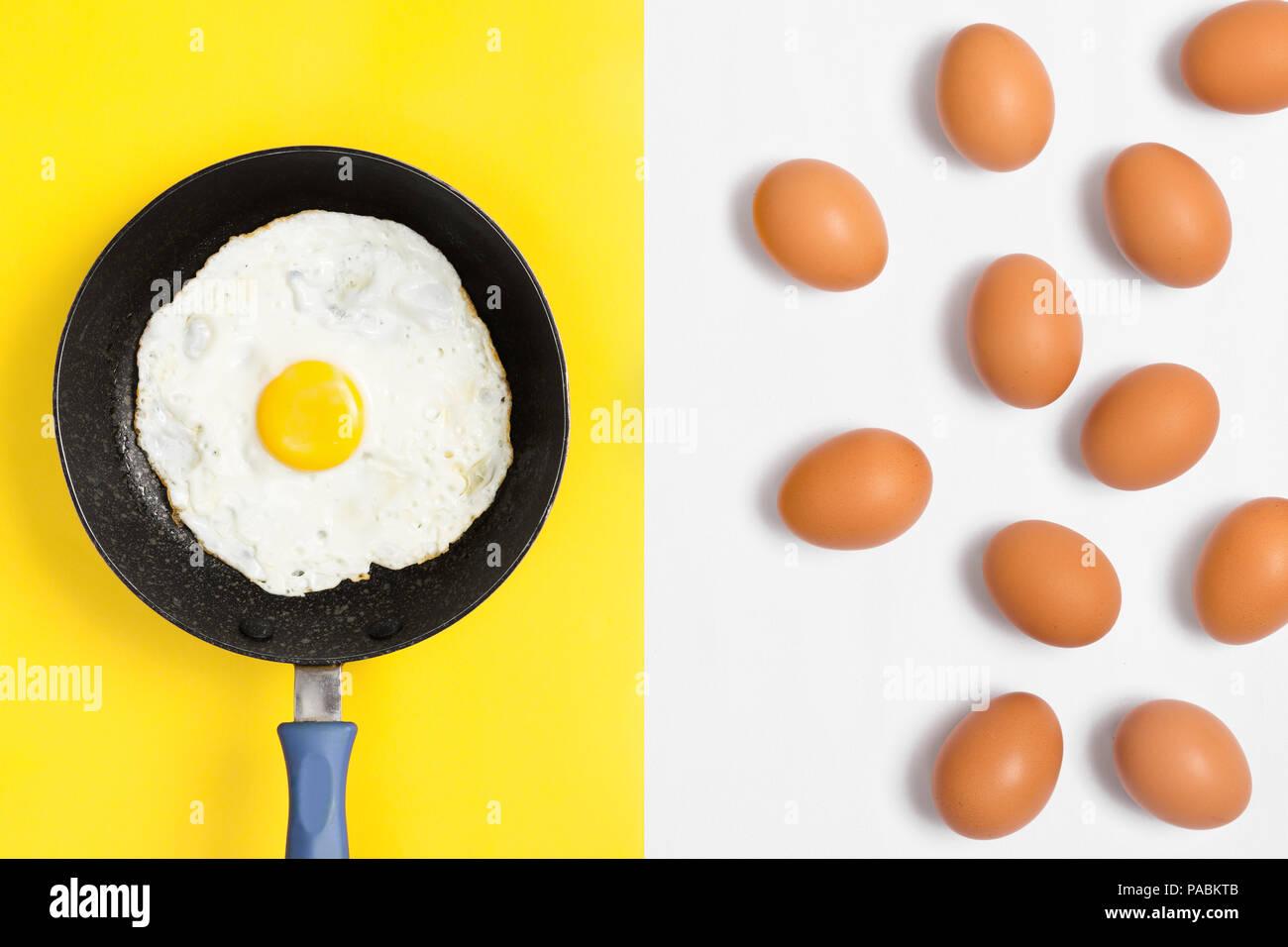 Frisch gekochtes Ei in einer Pfanne mit Ungekochte Eier zufällig über weißen Hintergrund platziert. Flach Bild. Stockbild