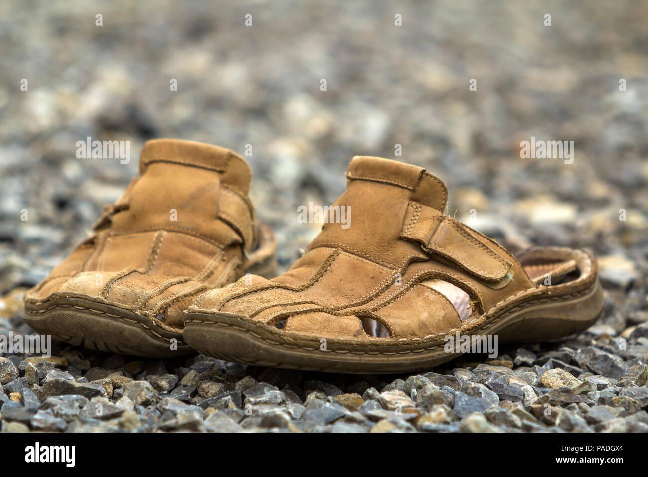 In der Nähe von paar alten, abgenutzten komfortable Mann Klassische Leder  weiche braune Sommer Schuhe Sandalen an outdoor Stein Steinchen. Moderne  Kleidung ... df425cecbb