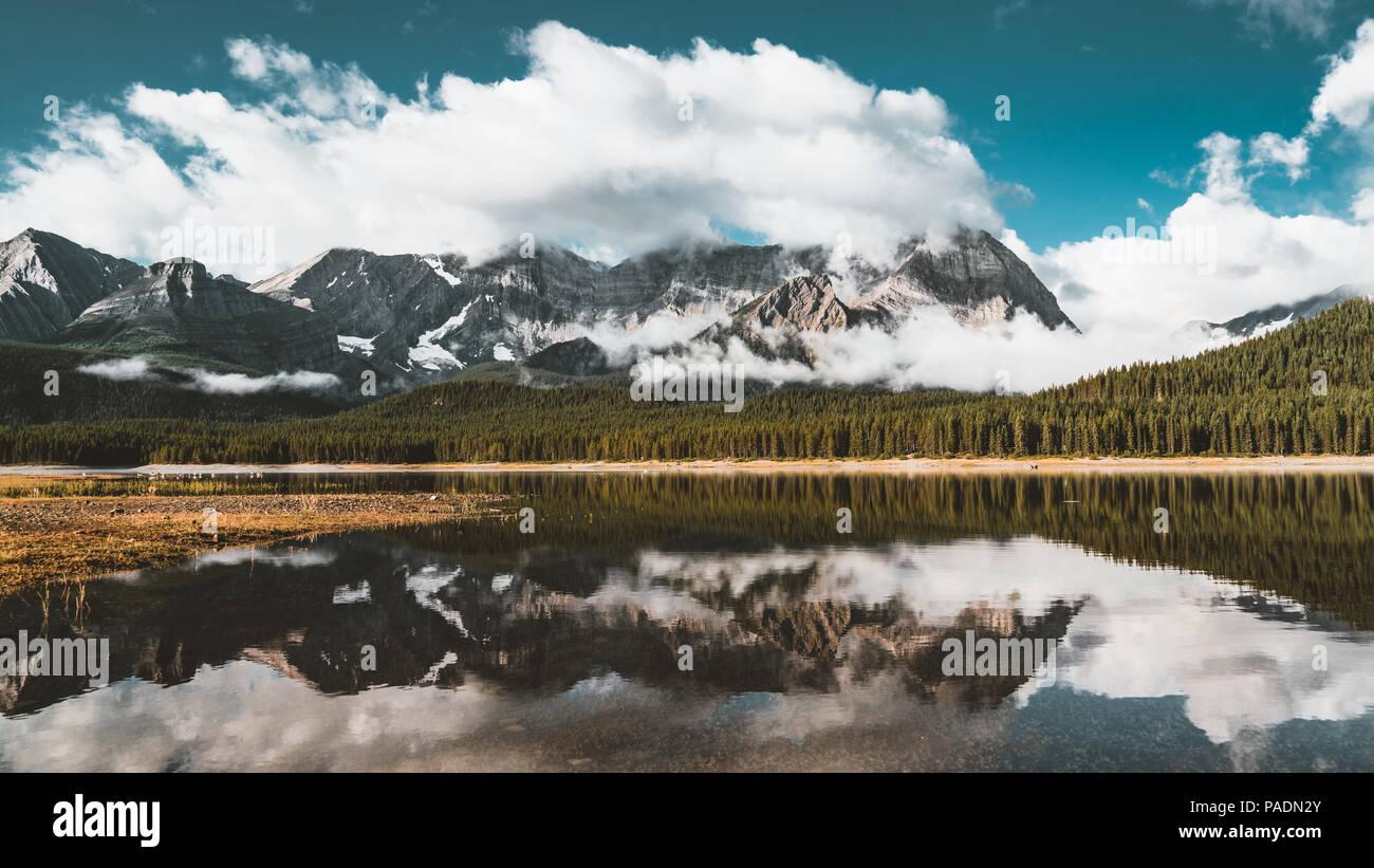 Reflexion mit See und Bergen niedrig hängenden couds im Lower Kananaskis See von Peter Lougheed Provincial Park Kananaskis Country Alberta Kanada Stockbild