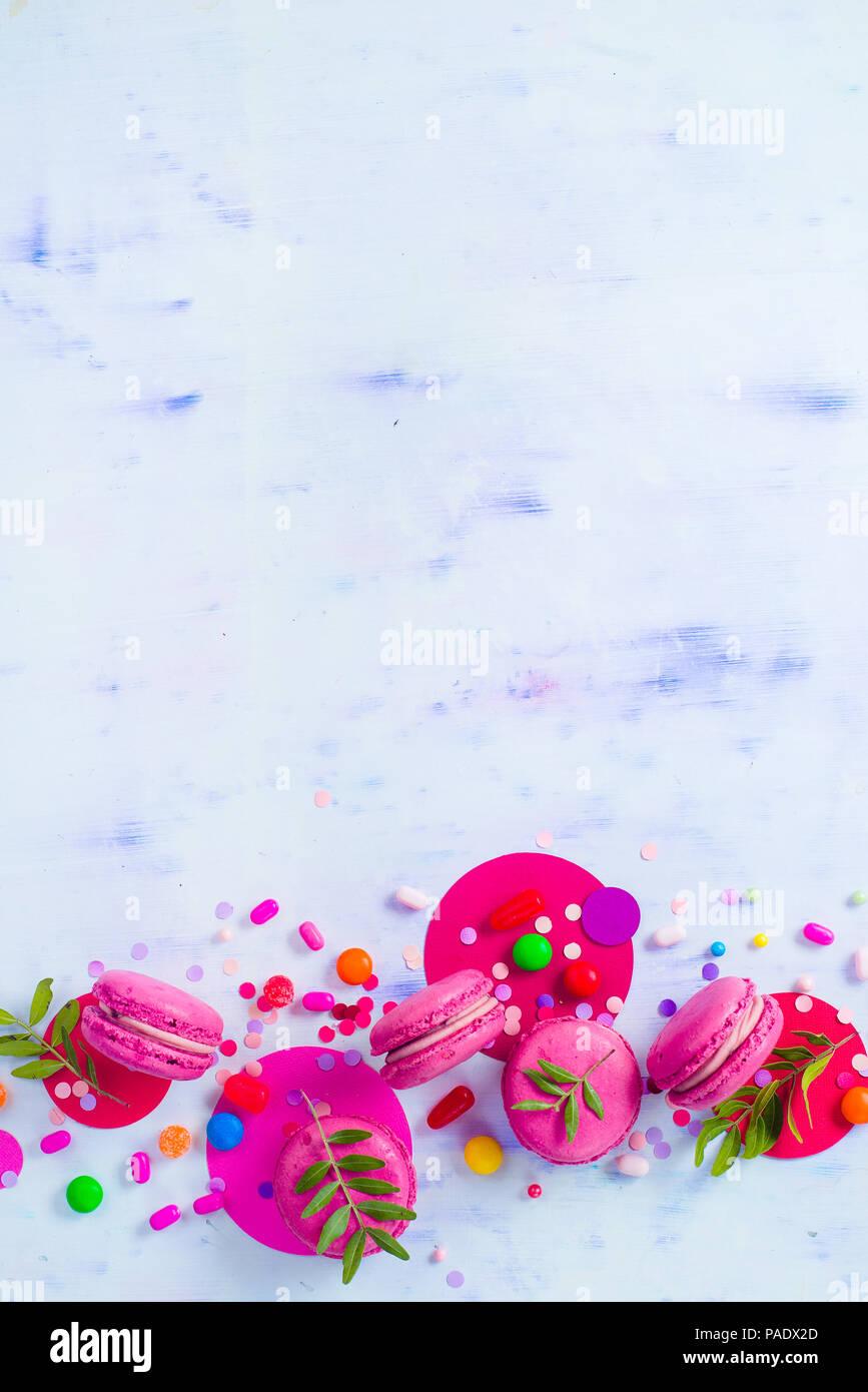 Macaroon Cookies auf einen farbigen Hintergrund mit Konfetti. Lebendige Partei Konzept mit kopieren. Rosa und Lila palette Flach. Stockbild