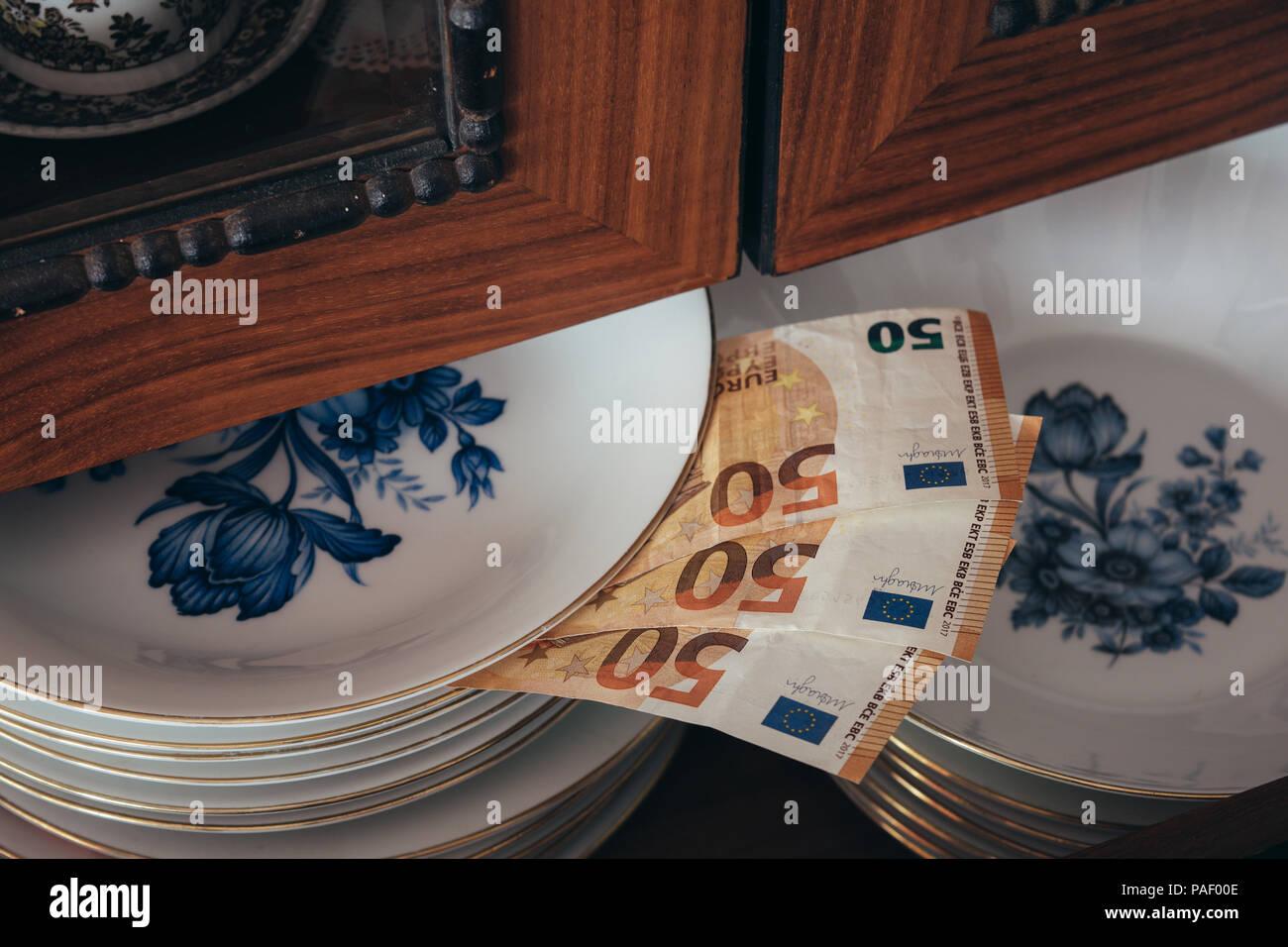 Geld sparen. Geld gespeichert zwischen den Platten. Ausblenden von Geld. Stockbild