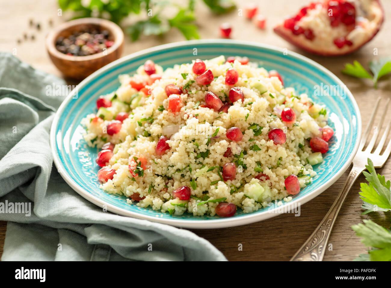 Gesunde couscous Salat tabbouleh mit Granatapfel auf Holz Tisch, Detailansicht, selektive konzentrieren. Ethnische arabisches Essen Stockbild