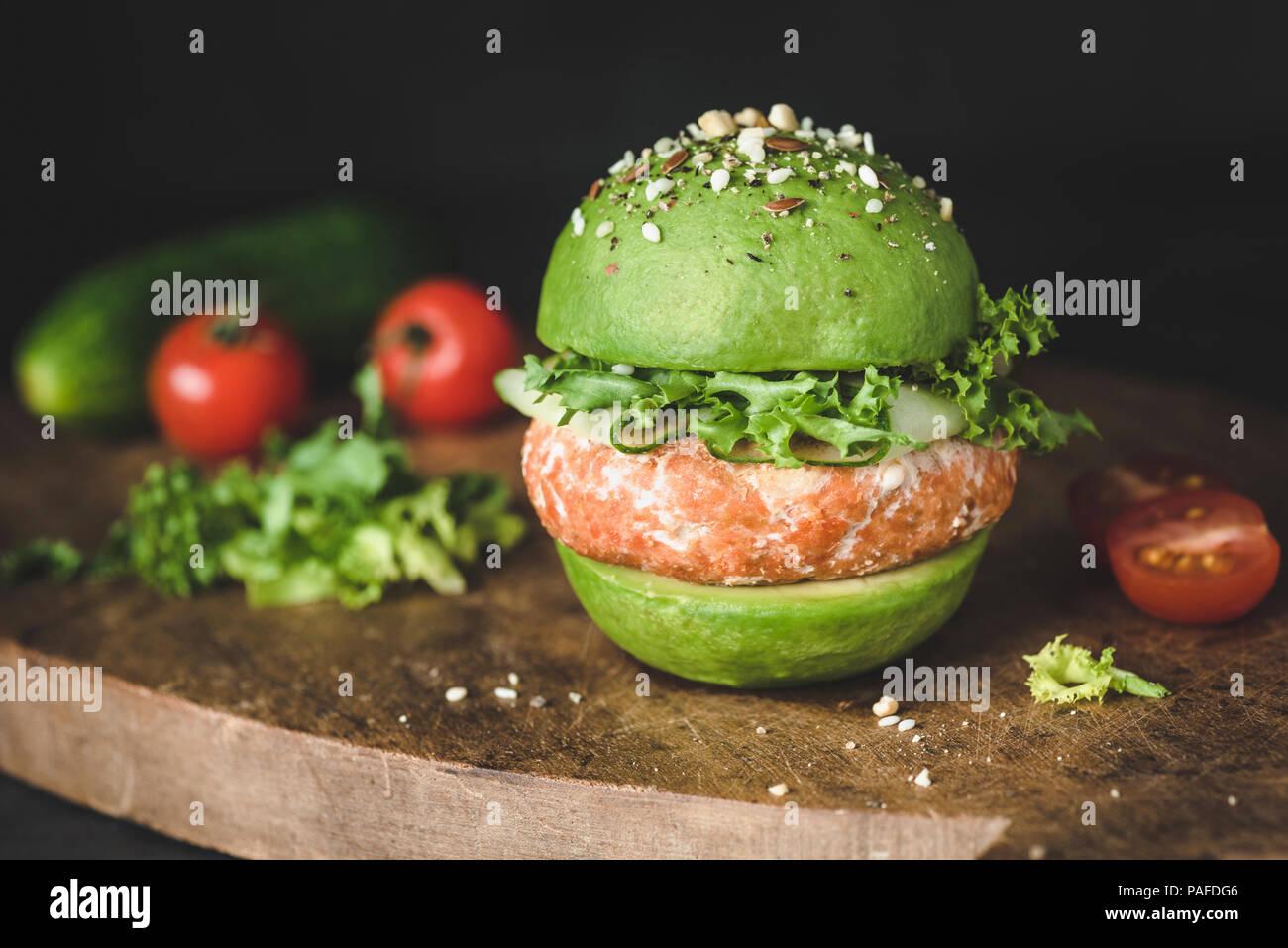 Vegan avocado Burger mit Linsen pattie auf Holz Schneidebrett, Detailansicht. Gesunde Burger Stockbild