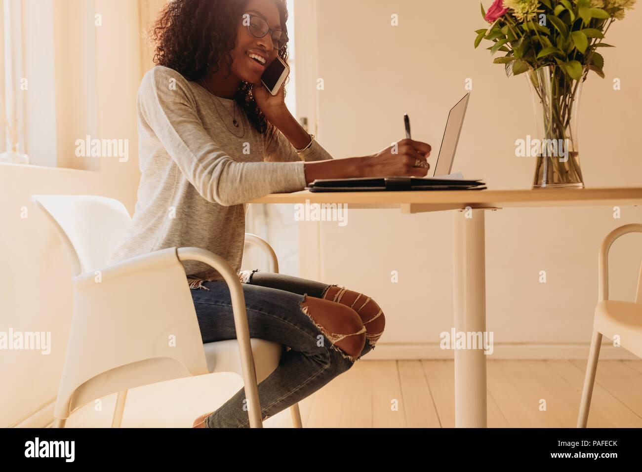 Unternehmerin verwalten Ihr Geschäft von zu Hause aus arbeiten am Laptop. In modischer Jeans zu Hause sitzen auf einem runden Tisch tal Geschäftsfrau Stockbild