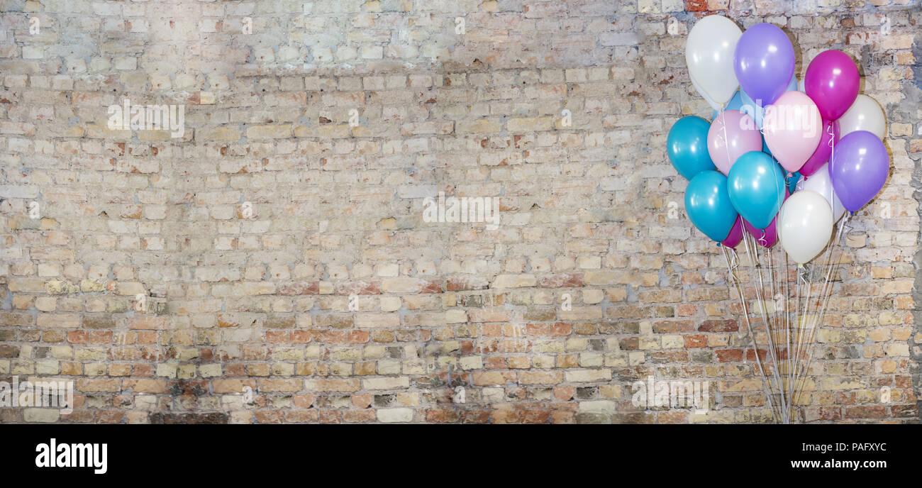 Eine Menge Luftballons an der Vorderseite der Ziegel Wand. Stockbild