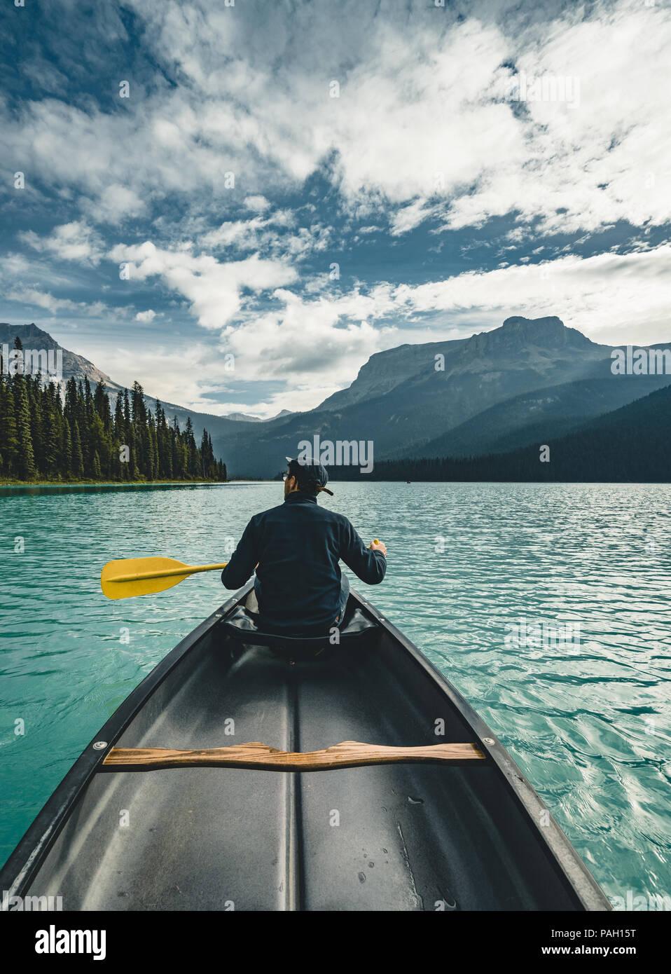 Junger Mann Kanufahren auf dem Emerald Lake in den Rocky Mountains, Kanada mit Kanu und die Berge im Hintergrund blaue Wasser. Stockbild