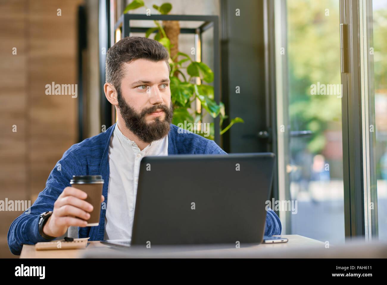 Attraktiver Mann mit Bart und blaue Augen arbeiten mit Laptop in der ...