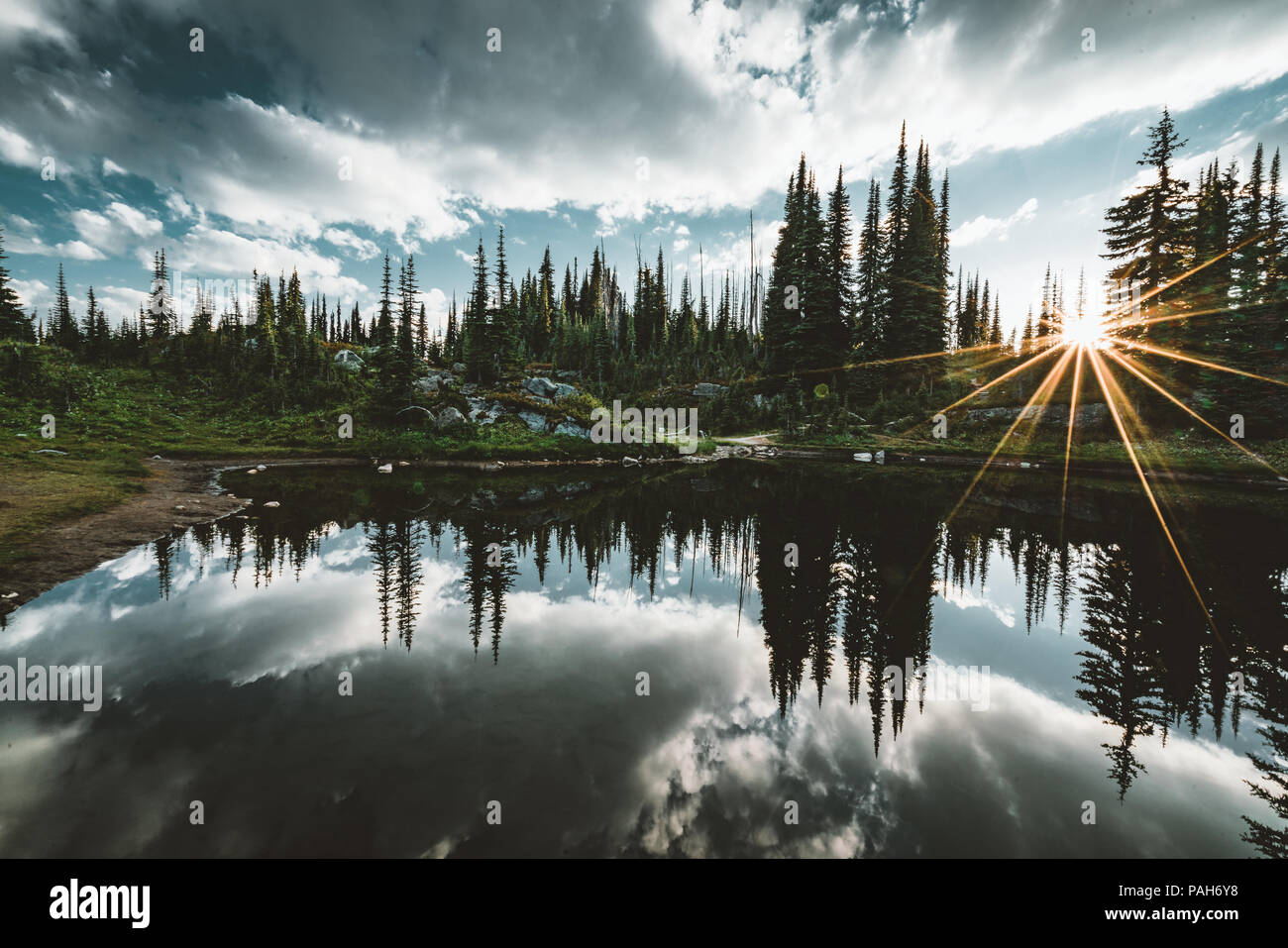 See auf dem Gipfel des Mount Revelstoke Sonnenuntergang Reflexion sunstar über Wald mit blauen Himmel und Wolken. British Columbia Kanada. Stockbild