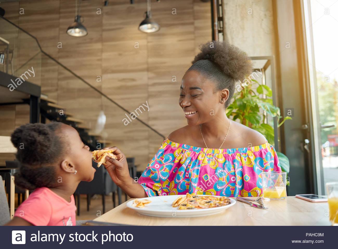 Lachend Mutter füttern Kind leckere Pizza im Loft gestalteten Restaurant. Lächelnd, gute Stimmung, tolle Zeit zusammen, sehr nette Familie. Andere Kunden in's Cafe Hintergrund sitzen. Stockbild