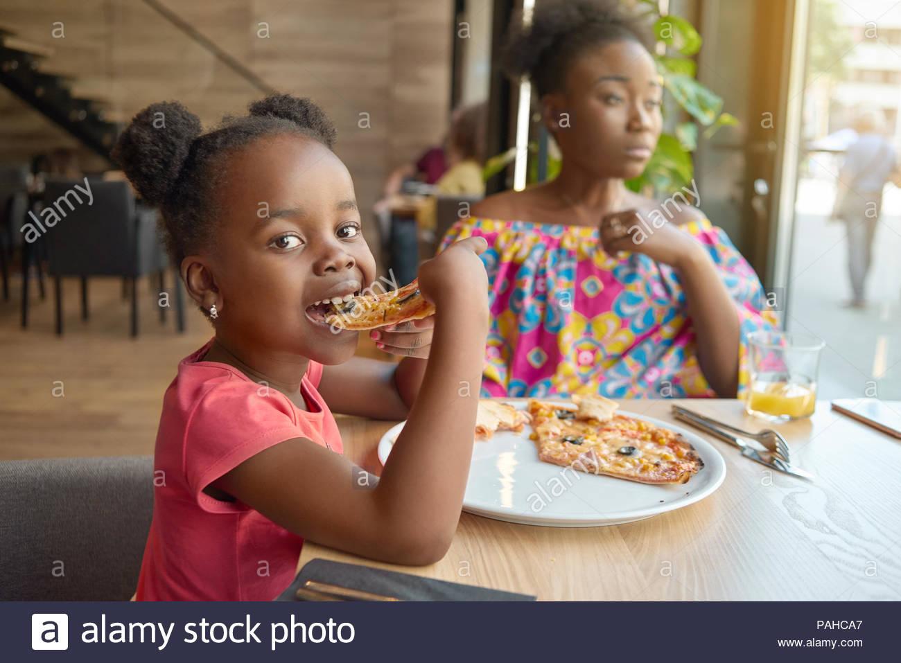 Hungrige kleine Mädchen essen Pizza in der Nähe ihrer Mutter sitzt im Cafe. Glücklich, gut gelaunt, wundervolle Zeit zusammen, sehr nette Familie. Andere Kunden in's Cafe Hintergrund sitzen. Loft design interieur. Stockbild