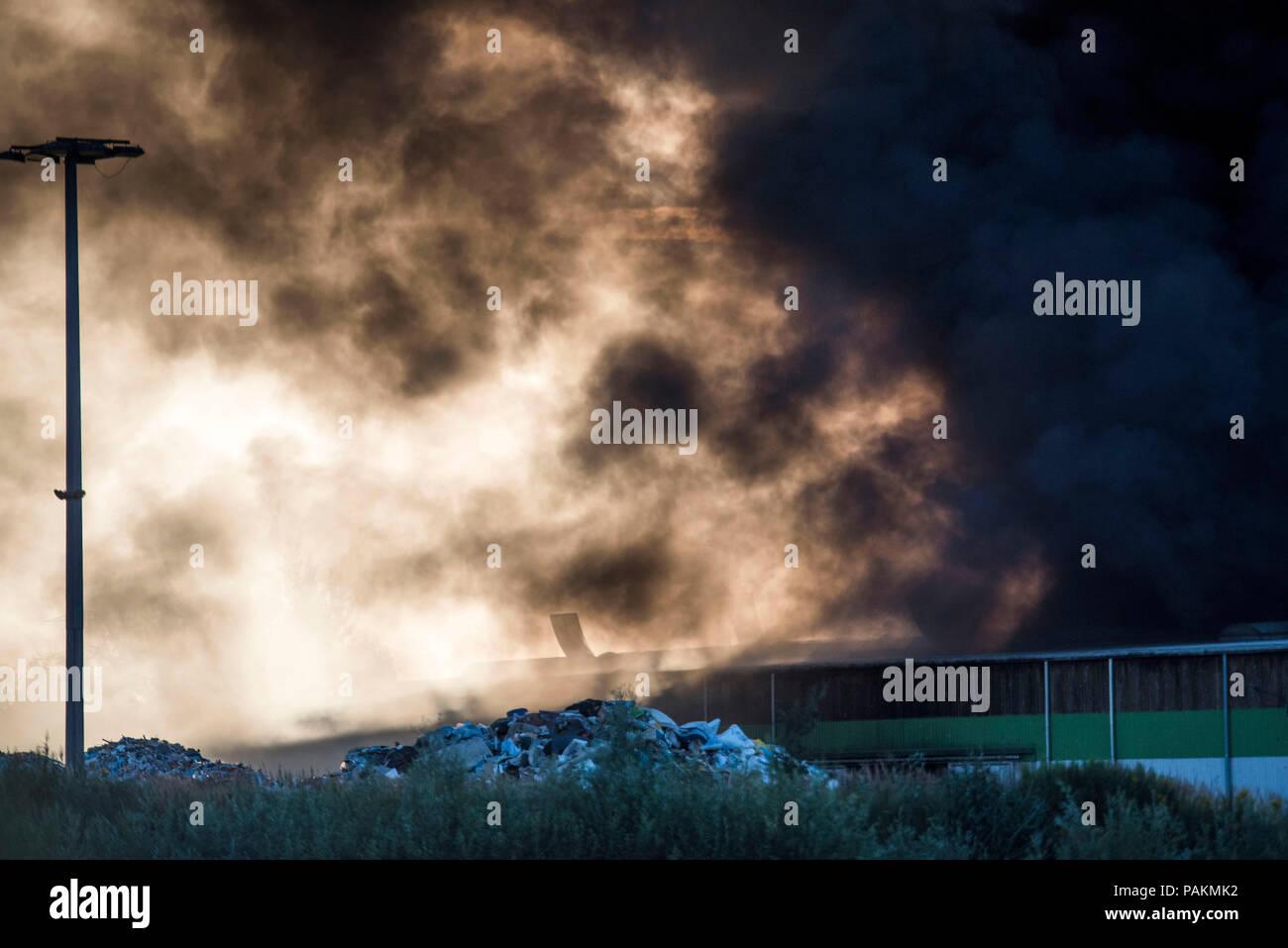 Rostock, Deutschland. 24. Juli, 2018. Dicke Rauchwolken steigen aus einem recyclinghof bei einem Brand. Nach Angaben einer Polizeisprecherin, Anfangs gab es keine Verletzten. Credit: Frank Hormann/dpa/Alamy leben Nachrichten Stockfoto
