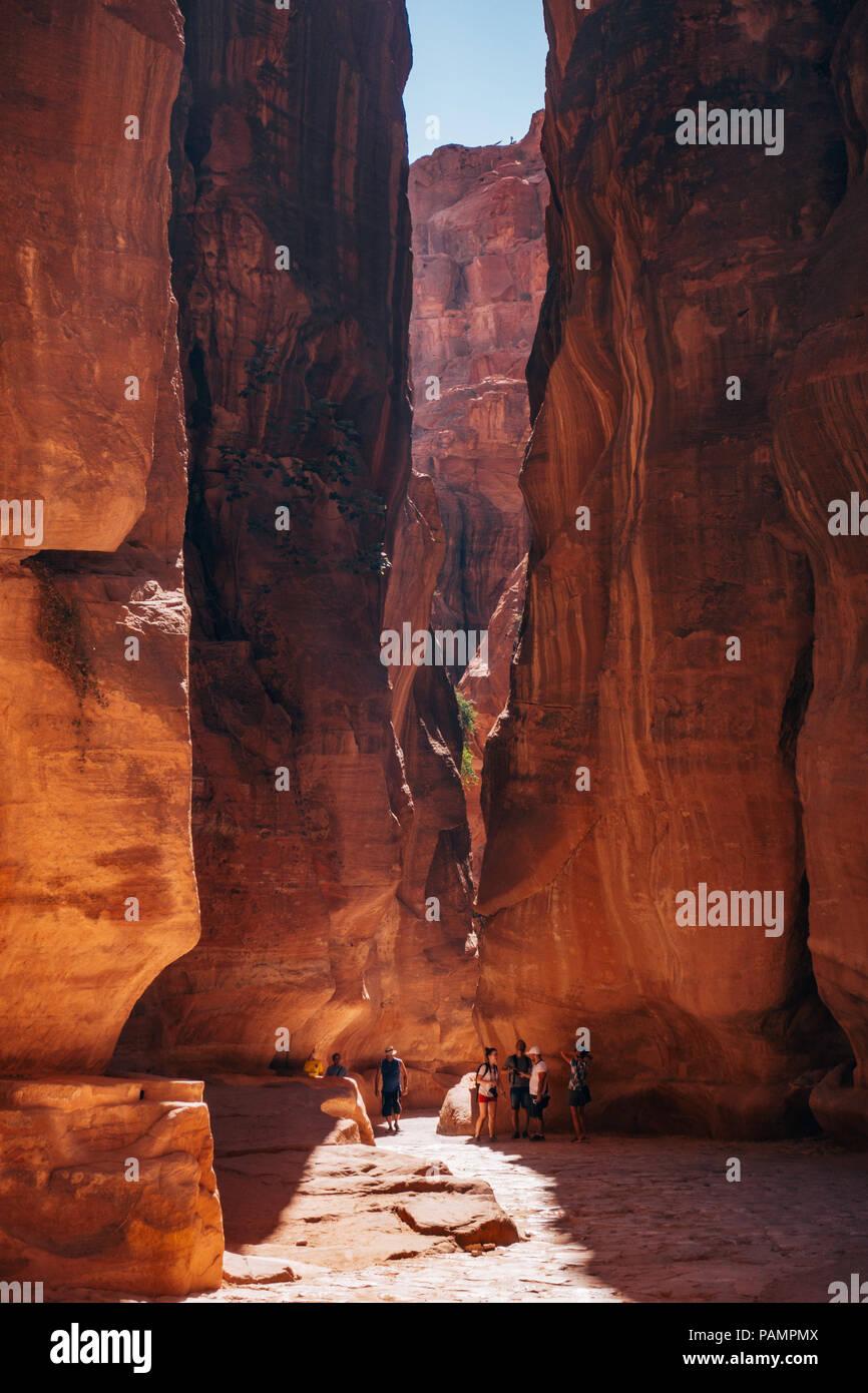Touristen werden durch die enge Schlucht auf dem Weg in die verlorene Stadt Petra, Jordanien in den Schatten gestellt Stockbild