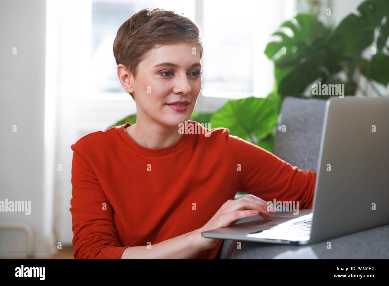 Frau sitzt zu Hause, mit Laptop Stockbild