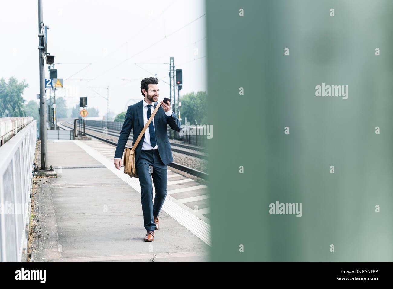 Lächelnd Geschäftsmann mit Mobiltelefon wandern an der Plattform Stockbild