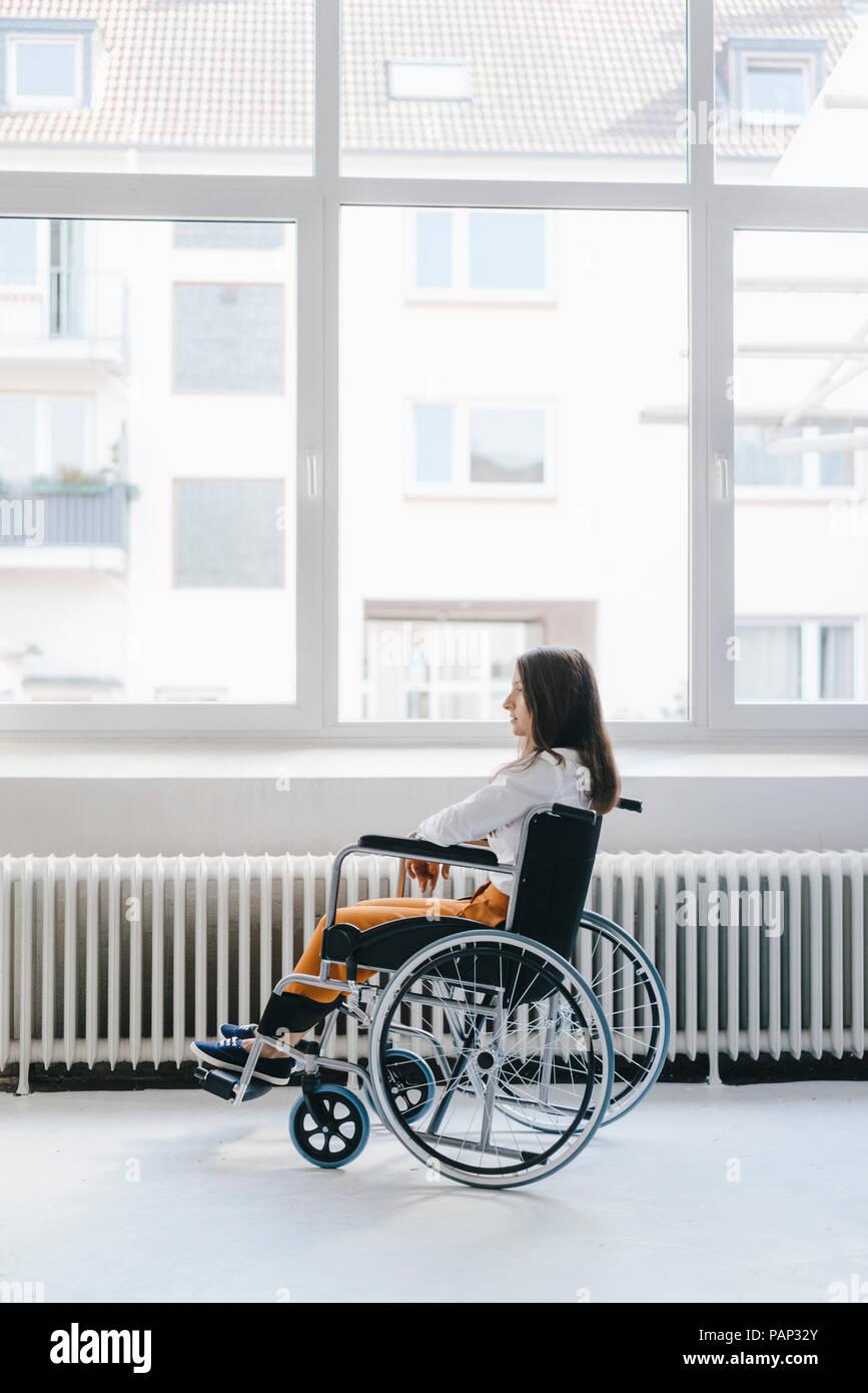 Junge behinderte Frau sitzt im Rollstuhl Stockbild