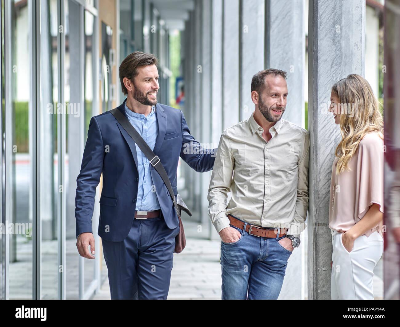 Geschäftsleute sprechen außerhalb Bürogebäude Stockbild