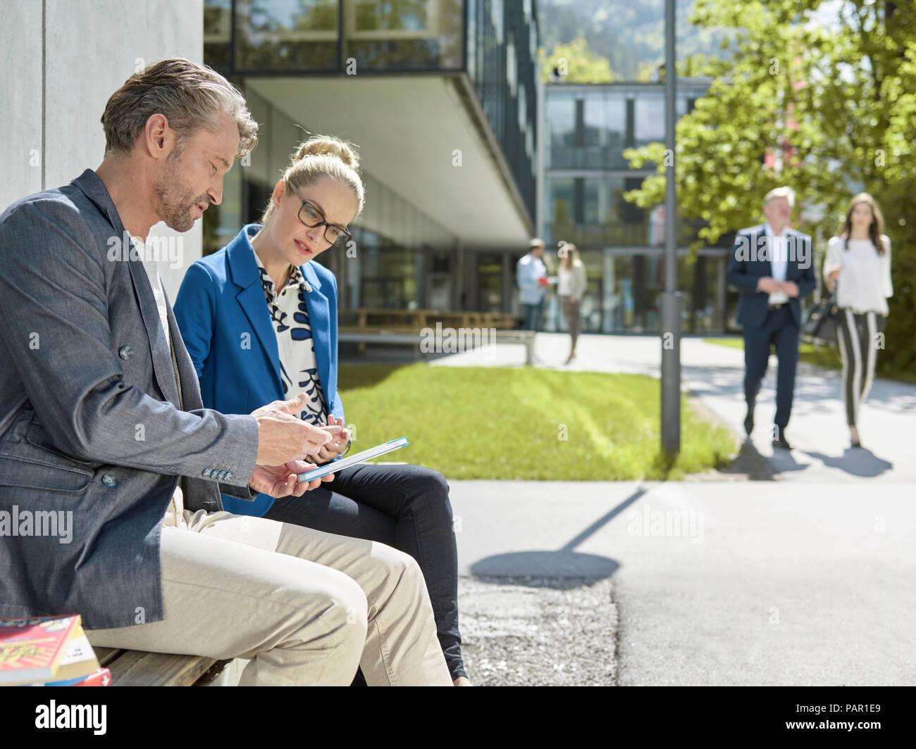 Kollegen mit Tablet sitzt auf der Bank außerhalb der Gebäude Stockfoto