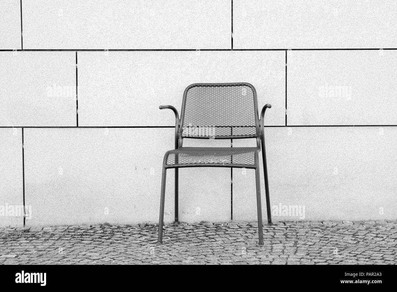 Ein Schwarz Weiss Foto Eines Leeren Metall Stuhl Gegen Eine Wand