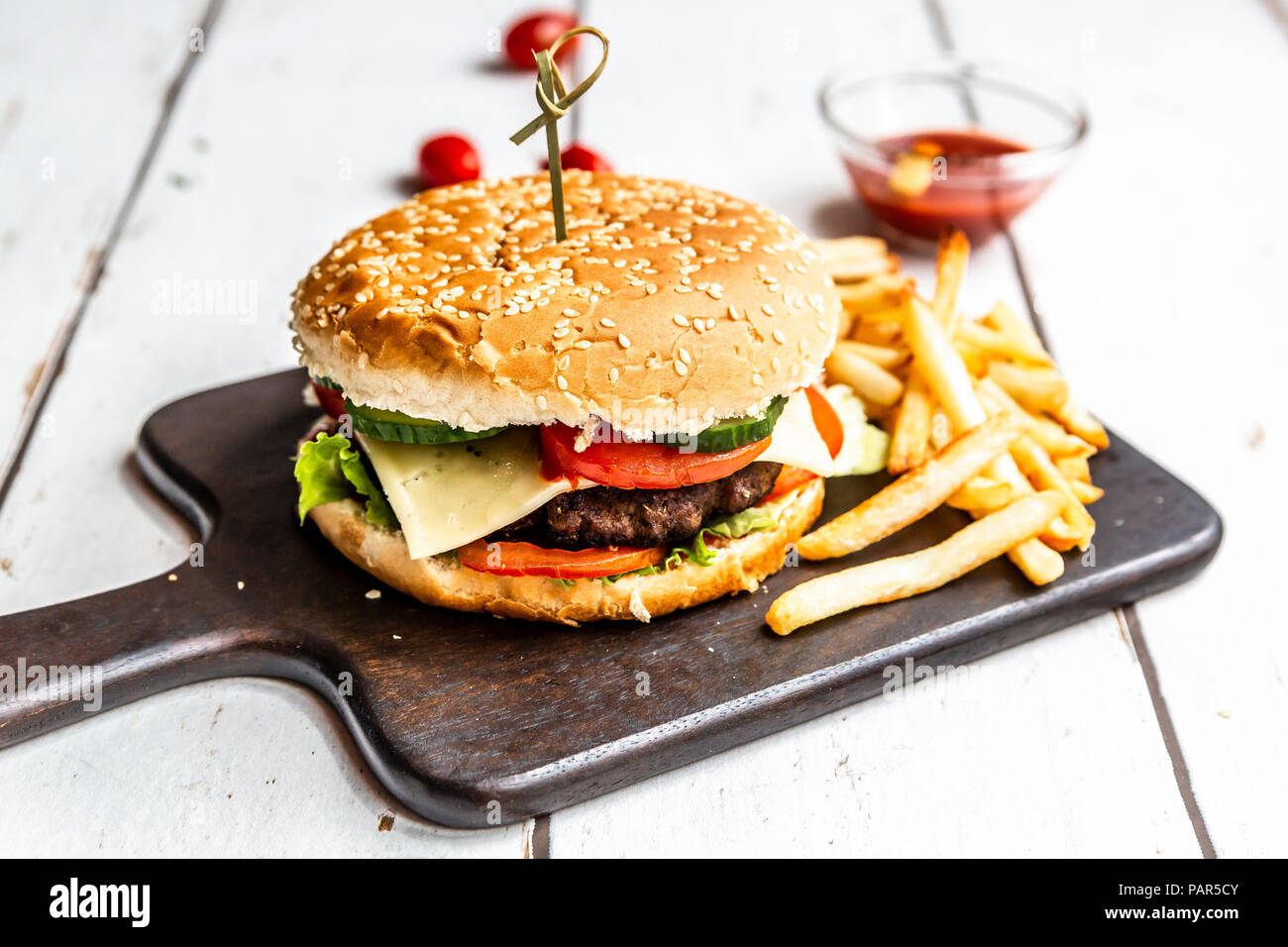 Hausgemachte Hamburger mit Käse, Pommes frites, Ketchup und Tomatenmark Stockbild