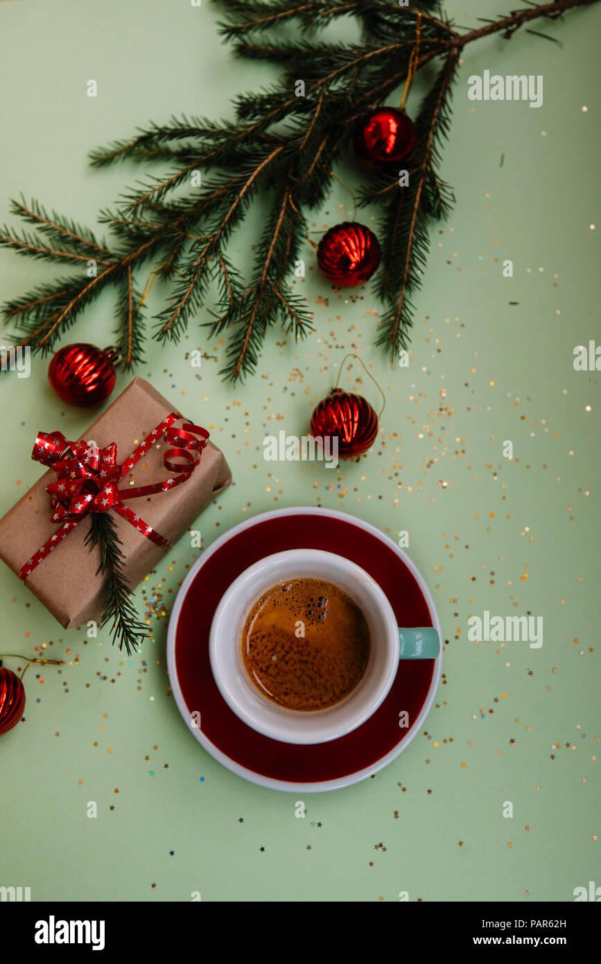 Leckere, frische Morgen winter festliche Espresso in eine grüne Tasse und Untertasse rot auf dem grünen Hintergrund mit Weihnachten Dekoration Stockbild