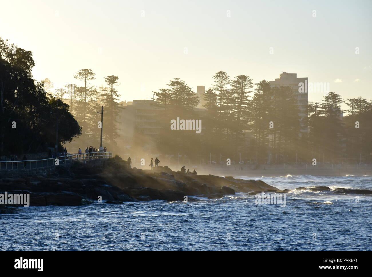 Nebel in Manly Beach kriechen. Die Menschen genießen den Sonnenuntergang und die letzten Sonnenstrahlen auf den Felsen. Stockfoto